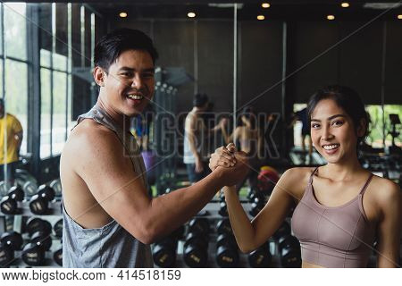 Healthy Asian Men And Women. They Work Out In The Gym. Athletes Collaborate With Trainers In Fitness