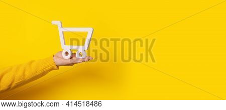 Shopping Cart On Hand Over Yellow Background, Panoramic Mock-up With Space For Text