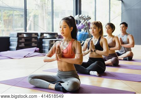 A Group Of Young Asian People Who Are In Good Shape Doing Yoga On A Yoga Mat With A Trainer Doing Th