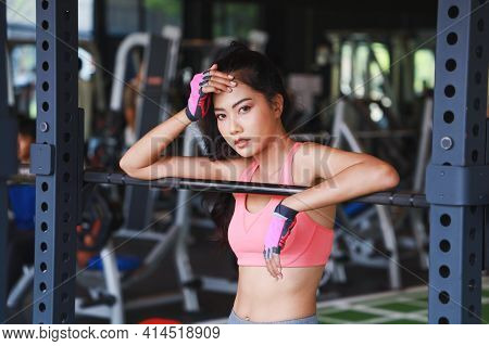 Asia Sexy Young Girl Resting After Squat Exercises In Fitness Gym.woman Wears Sportswear And Poses G