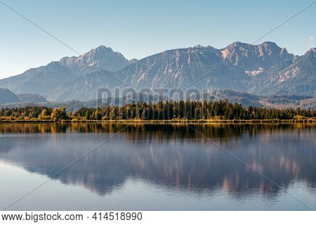 Soothing Reflections In Hopfensee Lake In Bavaria, Germany. View Of The Lake With Shining Trees And