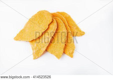 Five Slices Breaded Chicken Schnitzel Fillet Sliced On A White Background. Raw Chicken Fillet Sprink