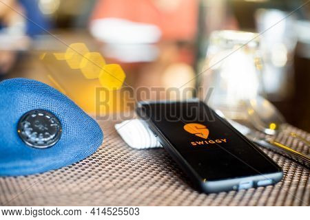 Blue Cloth Mask With Mobile Phone At Side With A Swiggy Logo In Restaurant Showing The Popularity Fo
