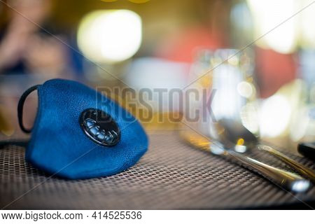 Blue Cloth Mask With Filter Placed On A Restuarant Table With Cutlery Knife And Fork Shot With An Ou
