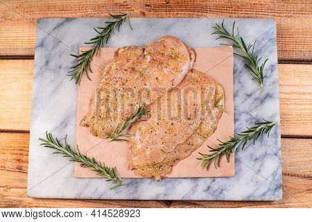 Chicken Fillet, Thinly Sliced, Sottilissime Marinated With Various Herbs On A Plate On A Marble Cook