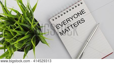Keyword Everyone Matters - Business Concept Text On White Notebook And Pen, Green Flowers