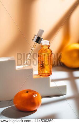 Glass Cosmetic Bottle With Oil Or Serum For Skin Care On Special Podium On Apricot Color Background.
