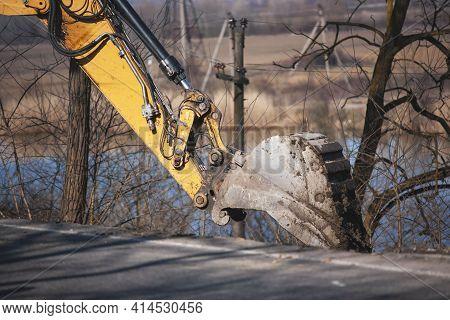 Repair Of An Asphalt Road After A Flood. Old Excavator Bucket. Excavator Makes Road Repairs