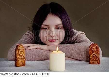 Girl Teenager 14-15 Years Old Sitting With His Head On His Hands, Looking At A Burning White Candle,