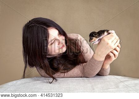 A 14-15 Year Old Teenage Girl Is Sitting, Holding A Small Puppy, Looking At It, Smiling.