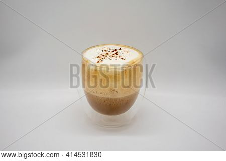 Hot Coffee With Milky Foam Sprinkle With Cocoa Power For Decoration In Double Wall Glass Isolated On