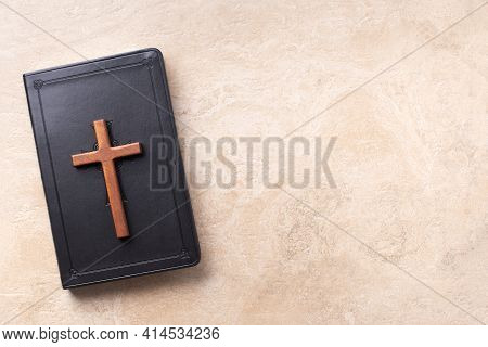 Wooden Cross On Bible Over Marble Background. Reminder Of Jesus Sacrifice And Christ Resurrection. E