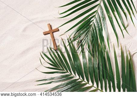 Palm Sunday Concept. Cross Made Of Palm And Tropical Leaves On Sand Background. Christian Moveable F