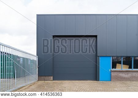 Small Industrial Warehouse With Roller Doors And Blue Entrance Door