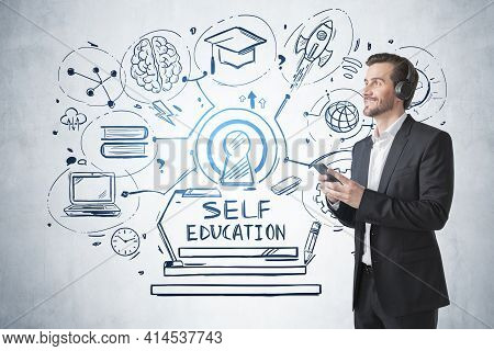 Young Positive Smiling Businessman Wearing Suit Is Learning And Studying By Listening Podcast Using
