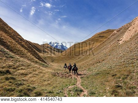 Riders With Weapons And Cargo Climb The Mountains On Horseback. Three Men On Loaded Horses Climb Up