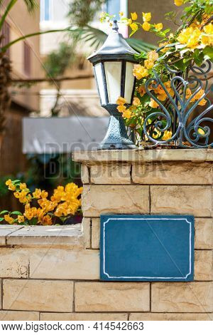 Shabby Brick Fence With Signboard And Street Lantern In Urban Garden With Blooming Yellow Flowers On