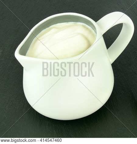 Small White Creamer With Cream On A Black Background.