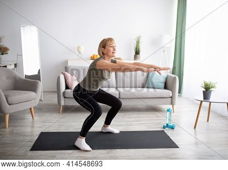 Home Training Concept. Active Mature Lady Doing Squats On Yoga Mat Indoors, Copy Space