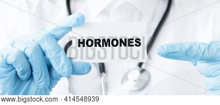 Hormones Text On Card And Hands Of A Doctor. Healthcare Or Prevention Concept.