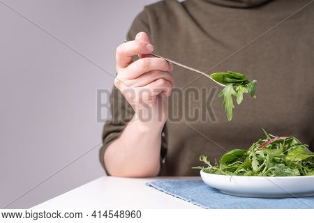 Female Hand Holding A Fork With Leafy Vegetables, A Plate Of Leafy Greens On A Wooden Table, Vegetar