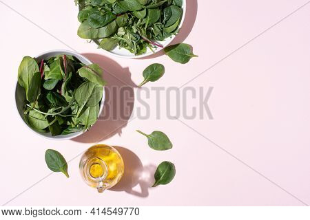 Plates With Leafy Greens, Olive Oil On Pink Background In Sunlight, Vegetarian Food, Healthy Eating,