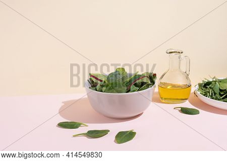 Bowl With Leafy Greens, Olive Oil On The Yellow-pink Background In Sunlight, Vegetarian Food, Health