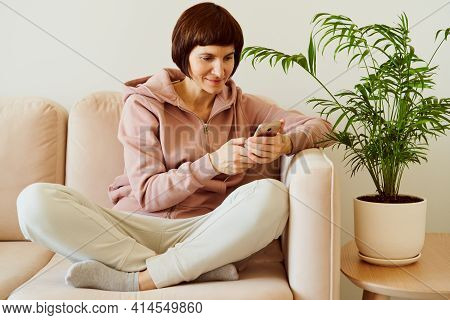 Middle-aged Female Sitting Cross-legged On Couch And Speaking By Audio-chat Looking Social Media