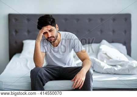 Bad Mood In Morning. Depressed Arab Guy Sitting On Bed And Contemplating About Problems, Copy Space