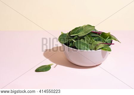 Bowl With Leafy Greens: Spinach, Beet, Arugula On The Yellow-pink Background In Sunlight, Vegetarian