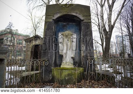 Stone Crypt With Headless Statue Of Angel And Metal Fence On Background Of Urban Houses - Smolenskoe