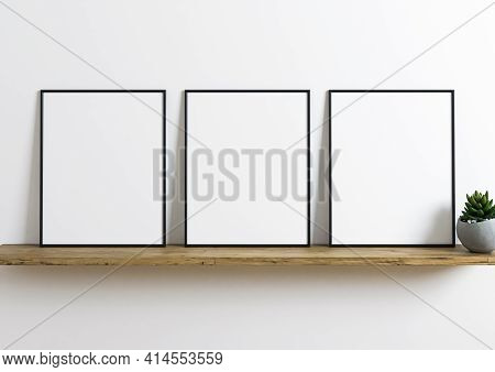Triple Black Frame Mockup On Wooden Shelf With Green Plant In A Vase And White Wall Behind It. Empty