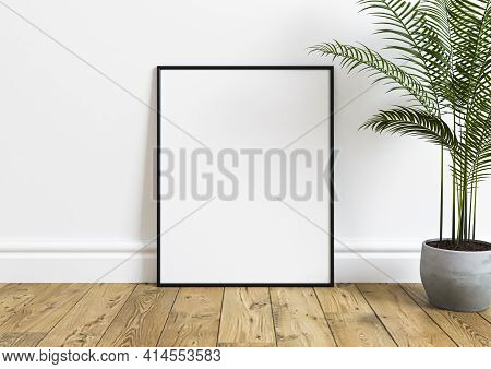 Black Vertical Frame Mockup On Wooden Floor With Green Plant In A Vase And White Wall Behind It. Emp