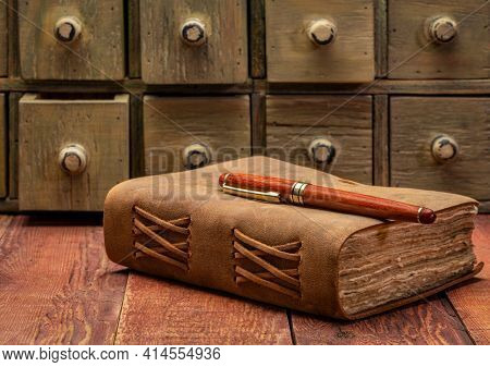 antique leather-bound journal or book with decked edge handmade paper pages and a stylish pen on a weathered barn wood table with rustic apothecary drawers