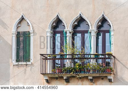 Facade Of Venetian Houses With Typical Old Venetian Windows On It. Sunny Day. Venice, Italy