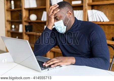 African American Sad Businessman Sitting At The Laptop In Medical Mask Covers His Face With The Hand