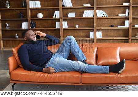 Portrait Of Smiling African American Man Lying On Leather Sofa In In A Spacious Room At Home, Using