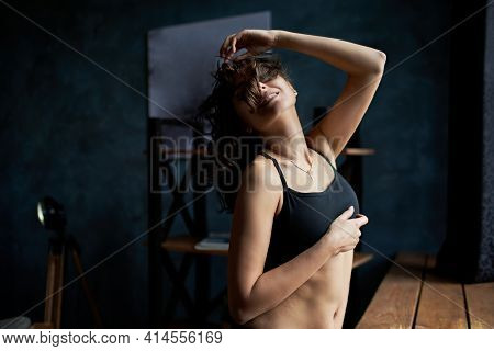 Beautiful Busty Girl In A Black T-shirt Smiles Sensually On A Black Background. Fashion, Advertising