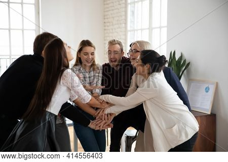 Overjoyed Multiracial Employees Stack Hands Involved In Teambuilding Activity