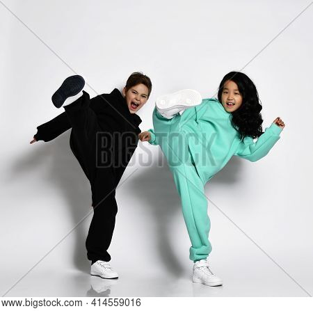 Fashionable Active Interracial Sporty Boy Girl In Warm Sportswear Jumping Together With High Kick Ki