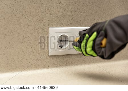 Installing Electrical Outlets. The Electrician Installs A Decorative Frame On The Electrical Outlets