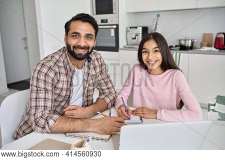 Happy Young Indian Parent Father Helping Teenage Child Daughter Distance Learning Online Together At
