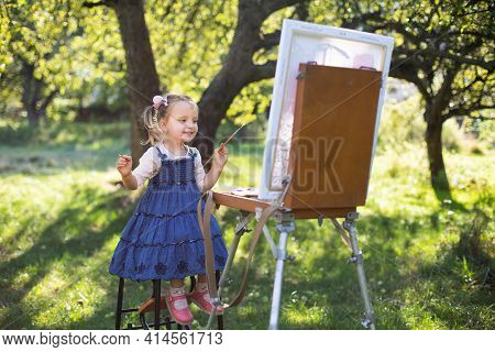 Little Artist. Easel And Painting On Canvas. Little Child, Cute 3 Years Old Girl In Jeans Dress, Pai