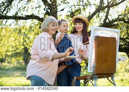 Easel, Canvas, Brushes And Paints. Family Leisure. Close Up Of Three Generation Family, Grandmother,