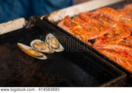 Process Of Cooking Mussels, Clams And Red Langoustine Shrimps, Prawns On Grill At Summer Local Food