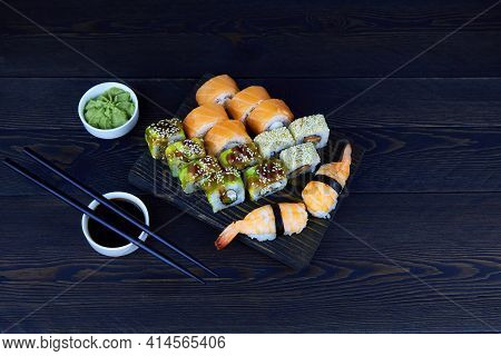 Assorted Japanese Sushi Food On A Dark Wooden Background. Sushi Roll Philadelphia With Salmon, Sushi