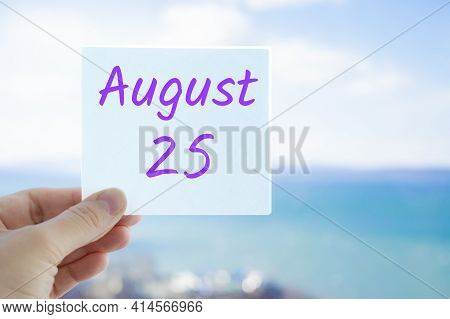 August 25th. Hand Holding Sticker With Text August 15 On The Blurred Background Of The Sea And Sky.