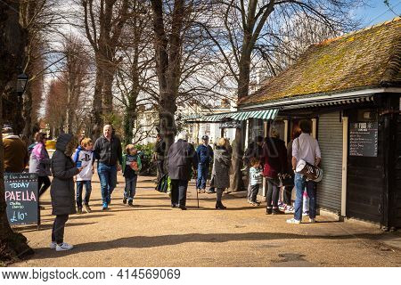 Canterbury, Kent, England - Mar 27 2021:people Stroll Past Don Juan Cafe In Dane John Gardens Park O