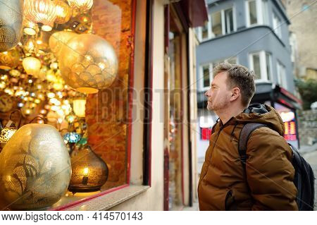 Mature Man Wearing Face Mask Looking Showcase Of Shop With Exotic Golden Ottoman Lamps On Street Of