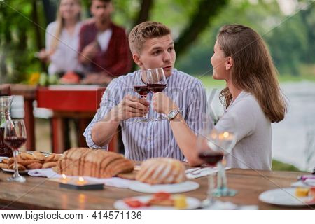 friends having picnic french dinner party outdoor during summer holidayfriends having picnic french dinner party outdoor during summer holiday